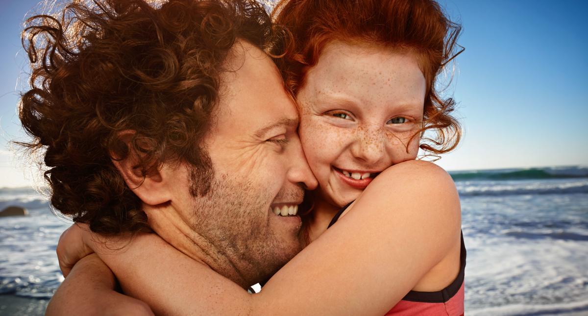 Girl (6 - 8) embracing father, close up
