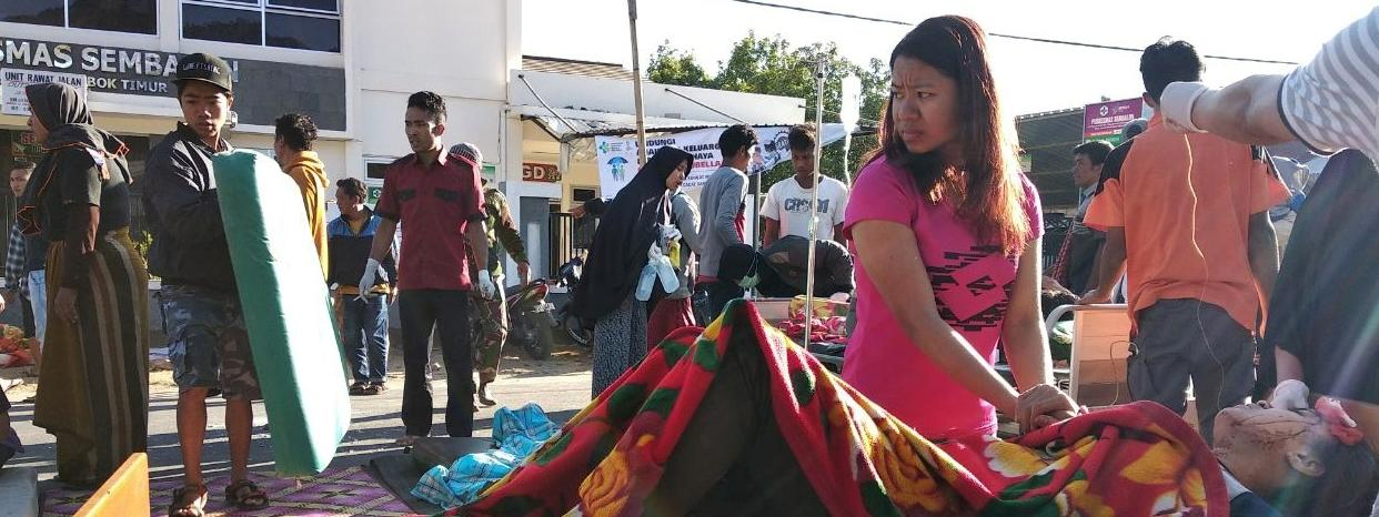 A woman stands near an injured person outside of a hospital after an earthquake hit Sembalun Selong village in Lombok Timur