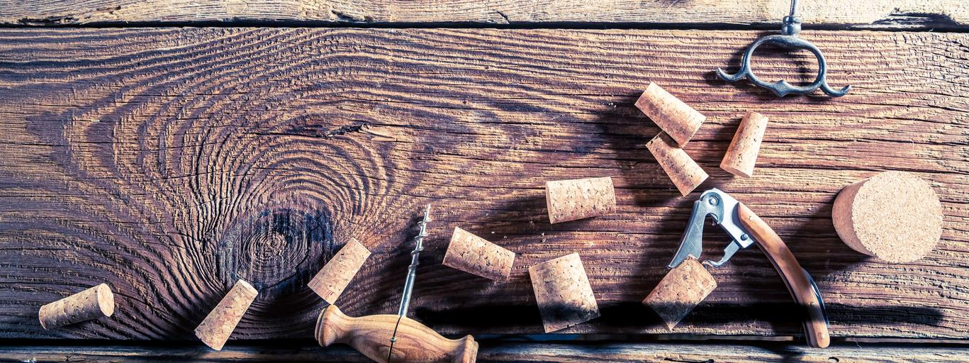 Corks from wine and opener on wooden table
