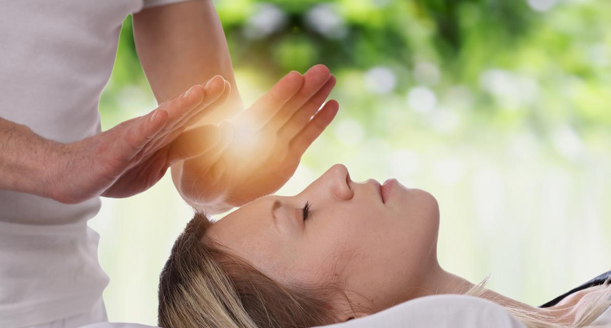 Woman having reiki healing treatment , alternative medicine concept.