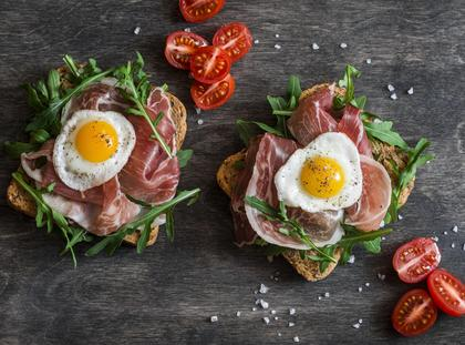Sandwich with prosciutto, arugula, and fried quail eggs on wooden background, top view. Tasty breakfast, snack or appetizer