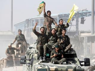 Syrian Democratic Forces (SDF) fighters ride atop of military vehicles as they celebrate victory in Raqqa