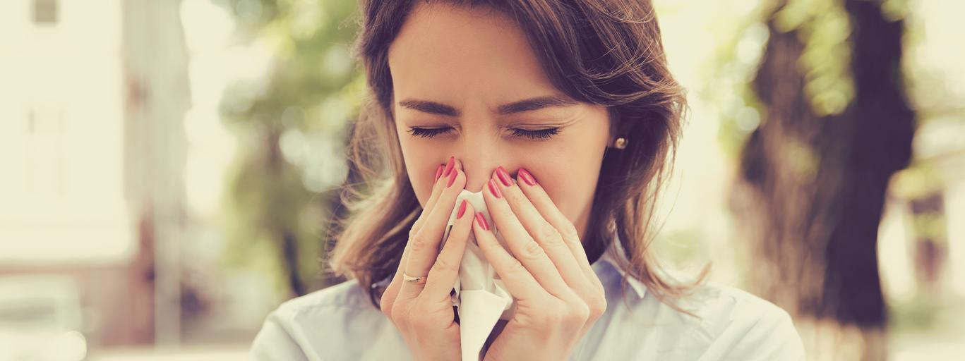 Woman with allergy symptoms blowing nose