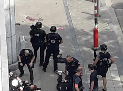 Police special forces are seen next to a man lying on the pavement and who supposedly was the shooter during a shooting in Liege