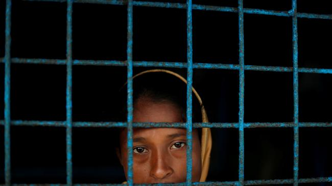 A Rohingya refugee who crossed the border from Myanmar this week stands at a window of a school used as a shelter at Kotupalang refugee camp near Cox's Bazar