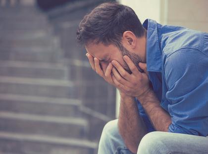 stressed sad crying man sitting outside