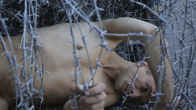 Pawlenski Pawleński Artist Pyotr Pavlensky lies on the ground, wrapped in barbed wire roll, during a protest action in St. Petersburg