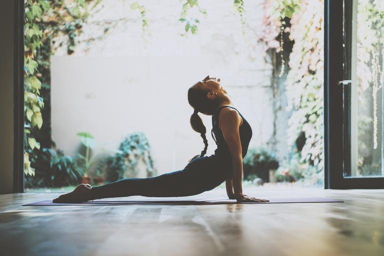 Portrait of gorgeous young woman practicing yoga indoor. Beautiful girl