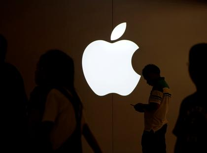 FILE PHOTO: A man looks at the screen of his mobile phone in front of an Apple logo outside its store in Shanghai
