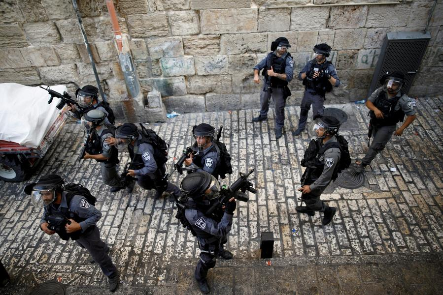 Israeli policemen guard a street at Jerusalem's Old city outside the compound known to Muslims as Noble Sanctuary and to Jews as Temple Mount, after Israel removed all security measures it had installed at the compound