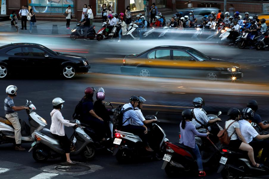 Motorcyclists stop at an intersection in Taipei