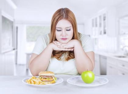 Confused woman choose apple or hamburger