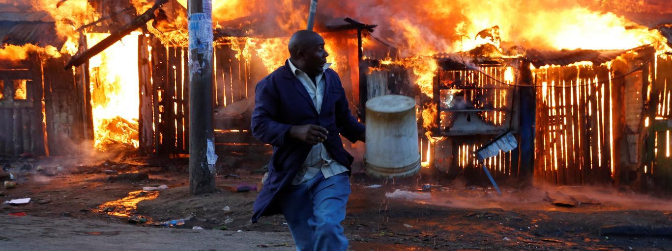 Mężczyzna ucieka z mieszkania, które zostało podpalone podczas zamieszek w slamsach Nairobii. Kenia
