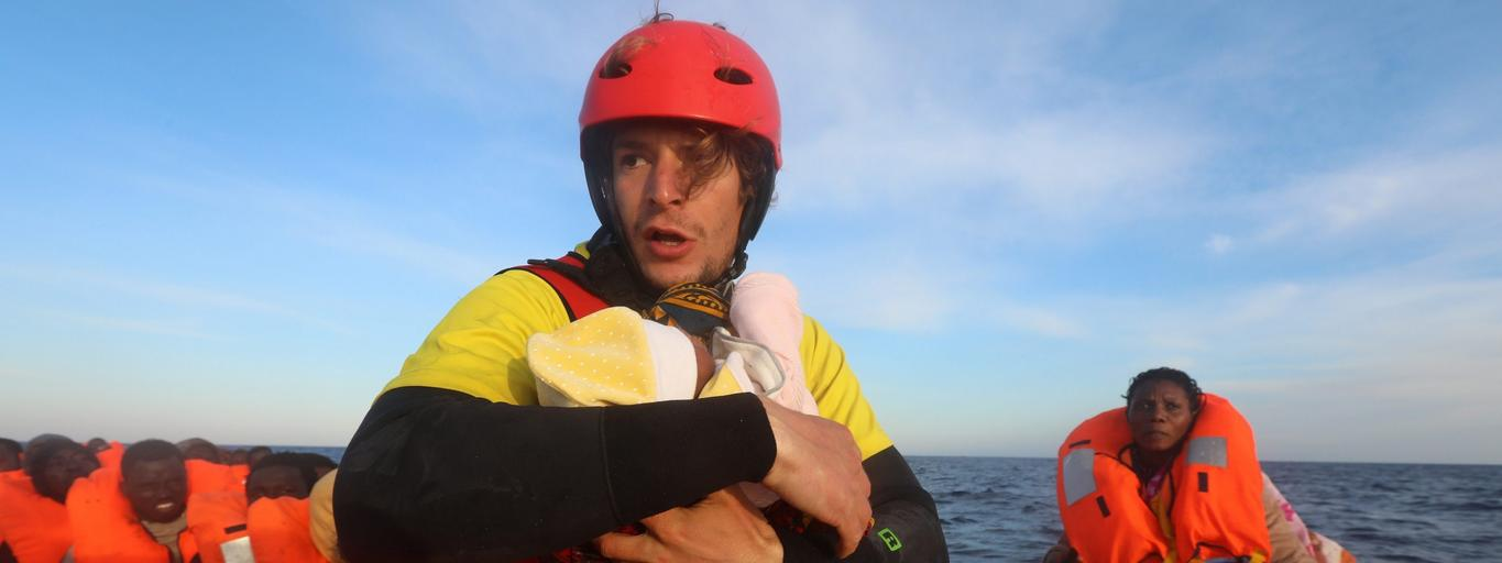 Spanish rescuer Daniel Calvelo carries a four-day-old baby girl into a RHIB, during a search and rescue operation by Spanish NGO Proactiva Open Arms, in central Mediterranean Sea, some 22 nautical miles north of the Libyan town of Sabratha