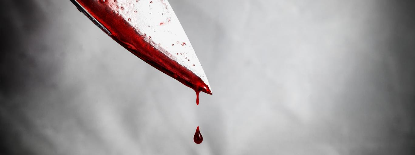 close-up of man holding knife smeared with blood and still dripping.