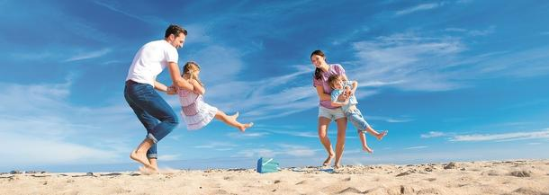 Parents Swinging Children at the Beach