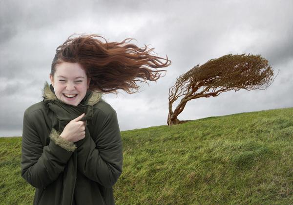 Young woman standing on windswept hill, smiling, eyes closed