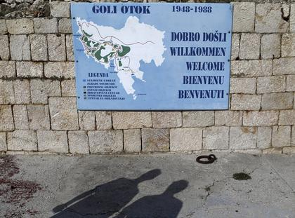 Visitors cast shadows on the ground as they look at the map of Goli Otok (Barren Island)