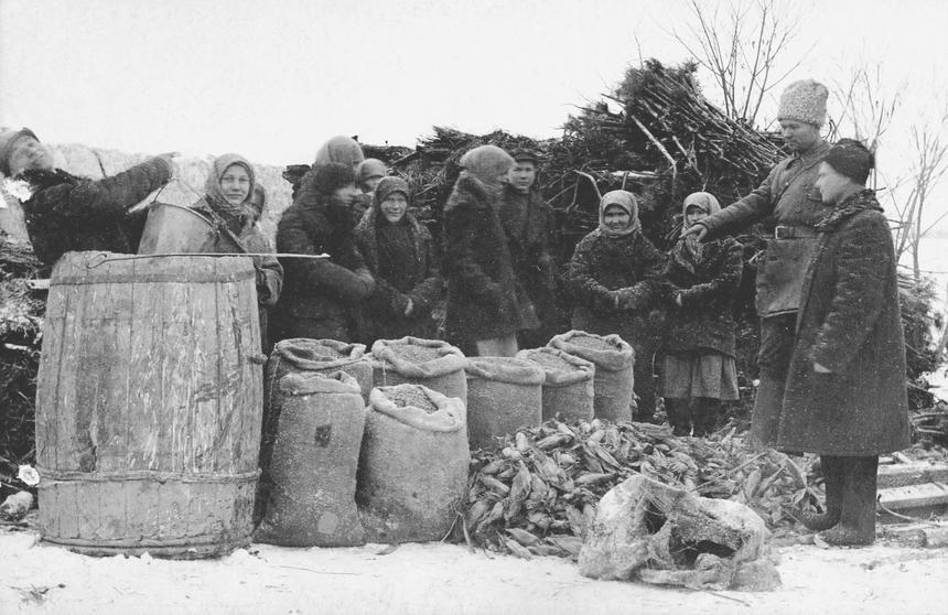 Brygada aktywistów demonstruje odkryte podczas przeszukań worki ze zbożem i kukurydzą