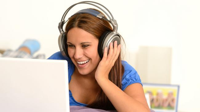 activity,adolescence,bed,bedroom,caucasian,cheerful,computer,enjoying,entertainment,fun,funny,girl,happy,headphones,indoor,internet,laptop,laughing,leisure,lifestyle,listening,lying,movie,music,relaxing,studying,surfing,teenager,using,watching,woman,young