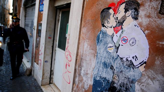 An Italian Carabiniere stands next to a mural depicting Northern League's leader Matteo Salvini and