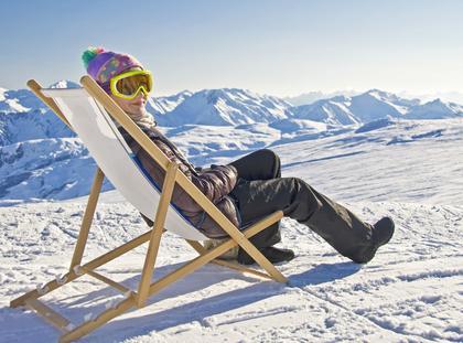 Girl sunbathing in a deckchair, snowy mountain landscape