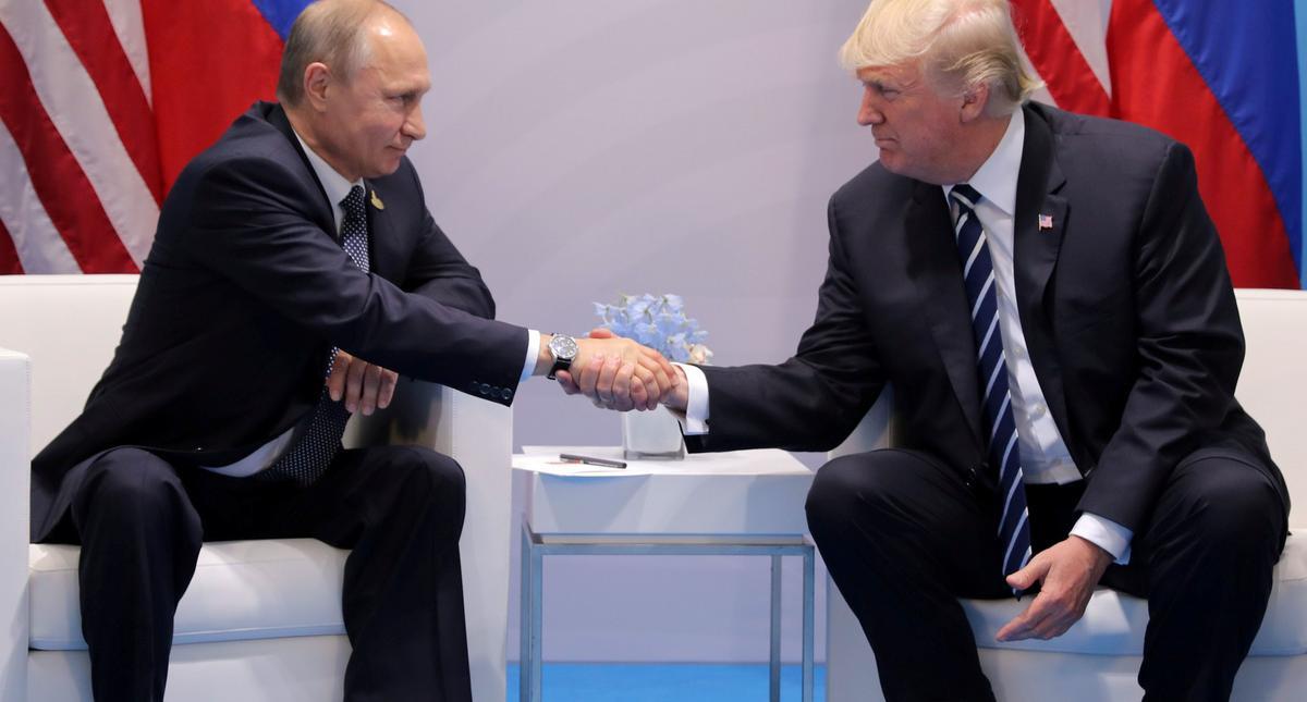 FILE PHOTO - U.S. President Donald Trump shakes hands with Russia's President Vladimir Putin during