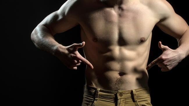 Man pointing fingers at his groin in jeans. Figure of athlete, naked male torso. The power of man. Male genitals or penis. Confident young guy