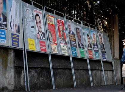 FILE PHOTO: A man looks at campaign posters of the 11th candidates who run in the 2017 French presidential election in Enghien-les-Bains