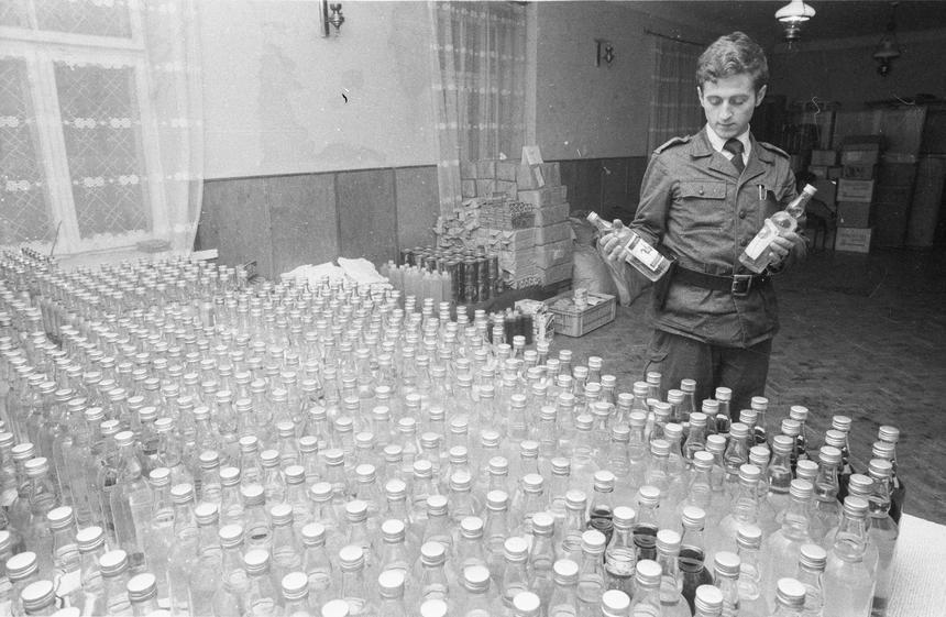 Góra Kalwaria, 1982-02-22. Funkcjonariusze Milicji Obywatelskiej z Biura do walki z przestępstwami gospodarczymi Komendy Głównej MO wspólnie z funkcjonariuszami MO z Góry Kalwarii zarekwirowali w mieszkaniu kierowcy prywatnej taksówki 1200 butelek alkocholu (w tym 400 butelek spirytusu), olej silnikowy, 2000 litrów etyliny 94, kilkadziesiąt kg mydła, 1000 paczek papierosów, pół tony cukru oraz duże ilości kaszy i mąki. Nz. Dzielnicowy Marian Sabała.
