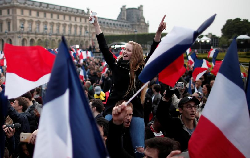 Supporters of Emmanuel Macron celebrate near the Louvre museum after results were announced in the second round vote of the 2017 French presidential elections, in Paris