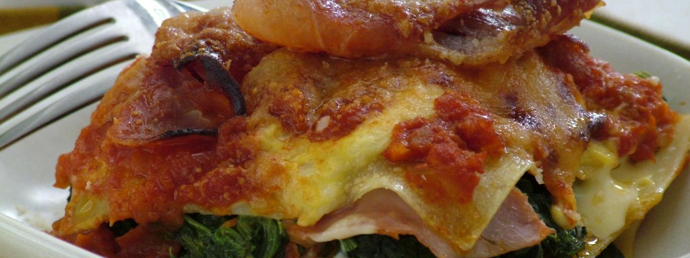 Portion of lasagne with parma ham, spinach and cheese