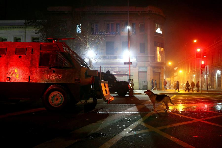 A dog barks at a riot police vehicle during a rally held to support women's rights to an abortion in Santiago,