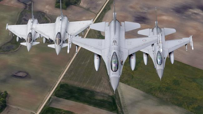 Norwegian Air Force's F-16 fighters and Italian Air Force's Eurofighter Typhoon fighters patrol over the Baltics during a NATO air policing mission from Zokniai air base near Siauliai
