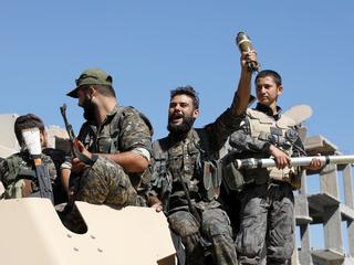 Fighters of Syrian Democratic Forces jubilate aboard an armoured fighting vehicle after Raqqa was liberated from the Islamic State militants, in Raqqa