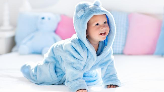 Baby in bathrobe or towel after bath on white bed