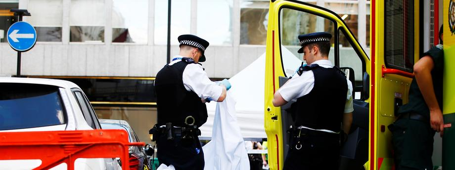 Police officers unfold a sheet infront of a body covered with a blanket after the London Ambulance Service reported that a man collapsed and died from a heart attack in the Mayfair district of central London