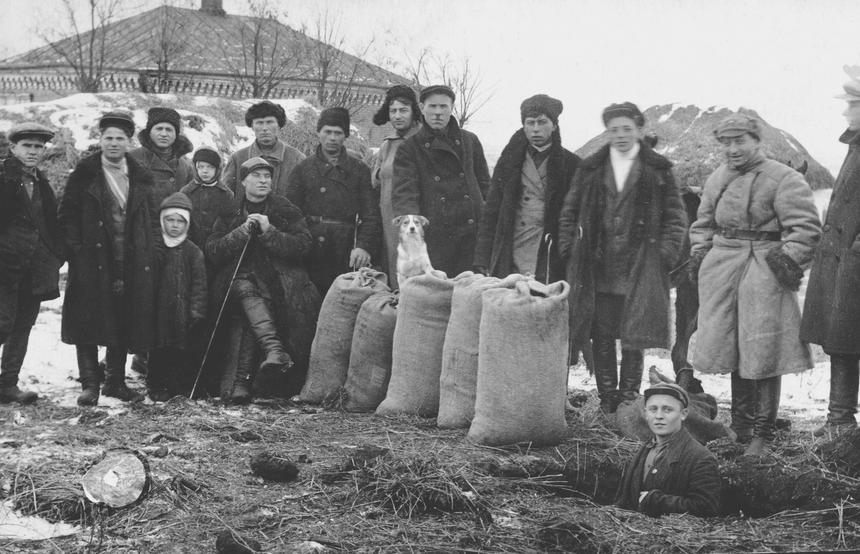 Brygada aktywistów znajduje schowane w ziemi ziarno. Przywódca trzyma żelazny pręt, którym posługiwano się podczas przeszukań