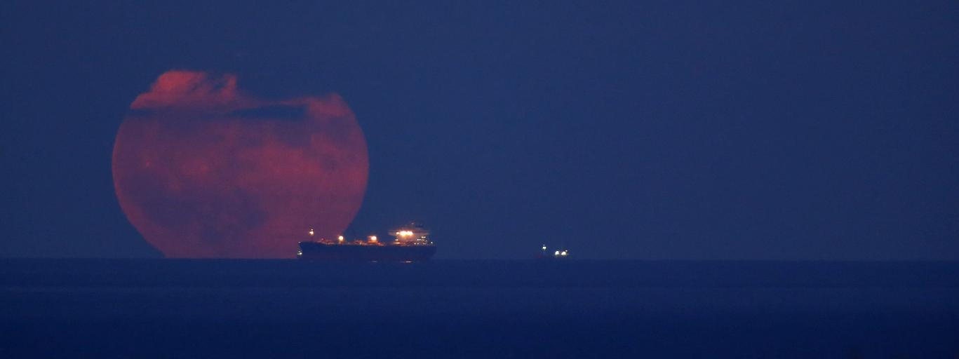The full moon rising behind an oil tanker anchored off Valletta is seen from San Gwann