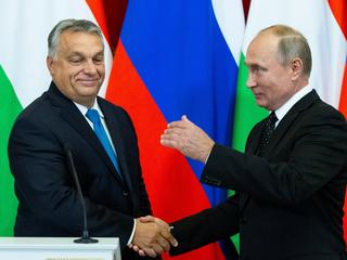 Russian President Putin shakes hands with Hungarian PM Orban during a joint news conference following their talks at the Kremlin in Moscow