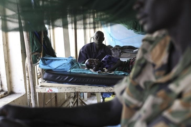 A child sick with malaria and from malnutrition lies on a bed in a hospital March 15, 2014. REUTERS/Andreea Campeanu
