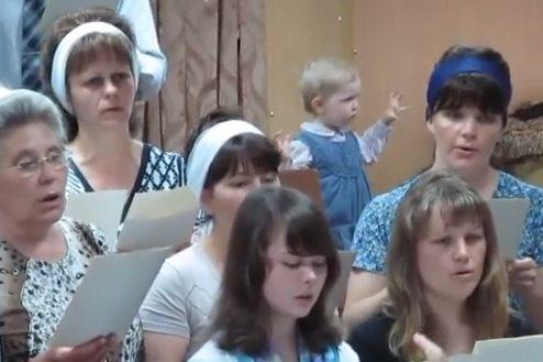 Mała dziewczynka dyryguje chórem.