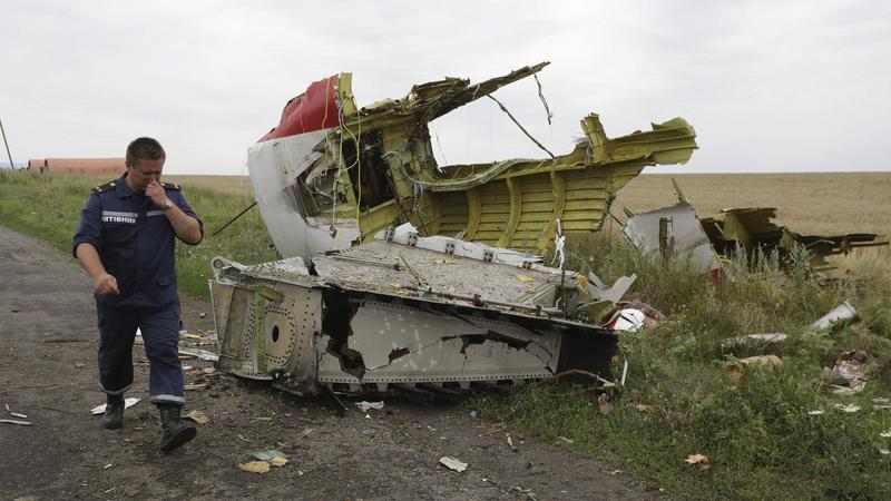 Członek ukraińskiej ekipy ratunkowej obok fragmentu zestrzelonego boeinga