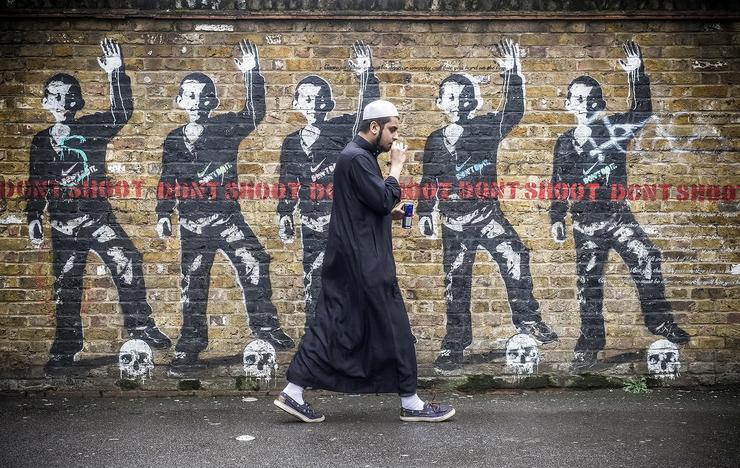 Ez a kép London egyik utcáján készült egy muszlim férfiról és a falfirkákról /Fotó: Nortfhfoto