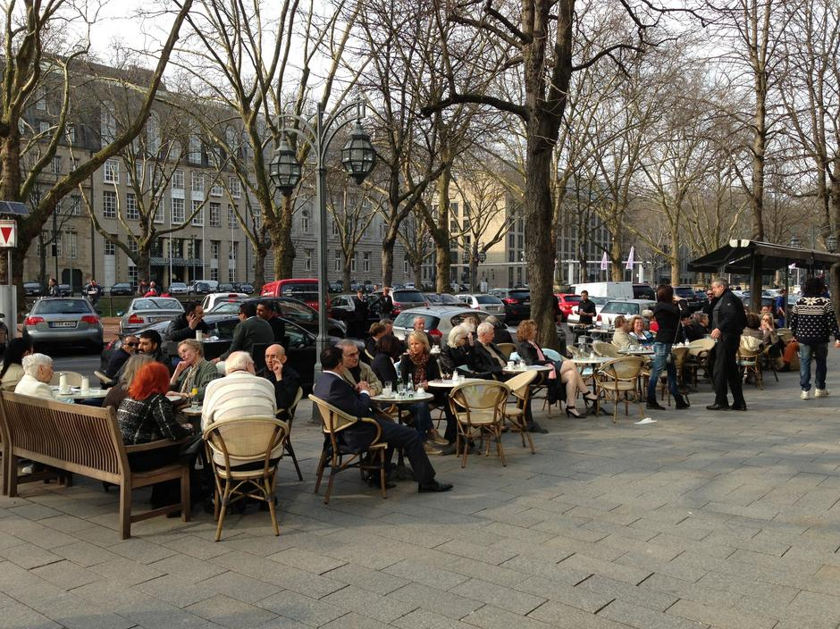 Mimo mroźnego dnia (początek marca), mieszkańcy miasta piją kawę na świeżym powietrzu.