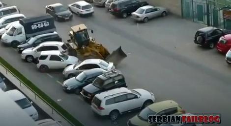Već slavni bager koji uništava niz automobila na parkingu