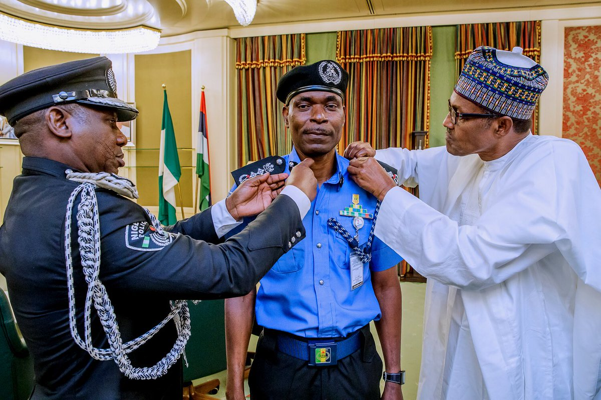 Mohammad Adamu (middle) decorated by Idris Ibrahim (left) and President Muhammadu Buhari (right) as the new Inspector-General of Police [Twitter/@NGRPresident]