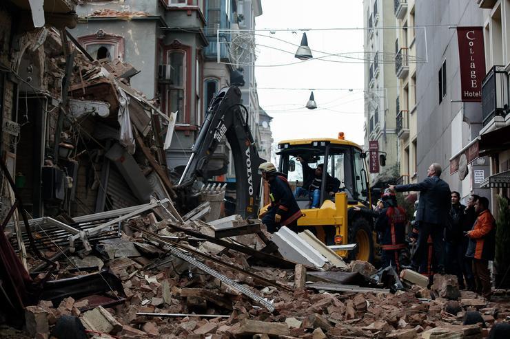 Tűzoltók dolgoznak két összeomlott ötemeletes épület romjai között - Fotó: MTI