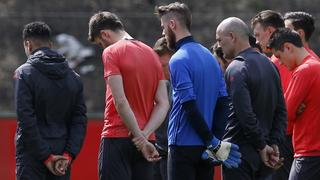 Manchester United players and staff stand for a minute of silence during training honouring the people killed and wounded in an explosion at Manchester Arena