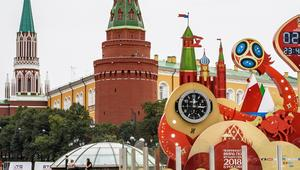 A couple walks in front of the digital FIFA World Cup 2018 countdown clock placed in front of the Red Square and the Kremlin in Moscow on September 13, 2017. FIFA announced that ticket sales for the 2018 World Cup will begin on September 14, 2017, nine mo